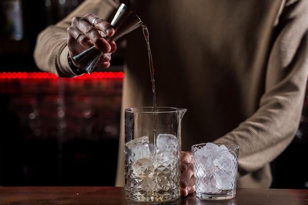 Barman maakt alcoholcocktail bij toog. barman maakt jungle juice-cocktail in bar