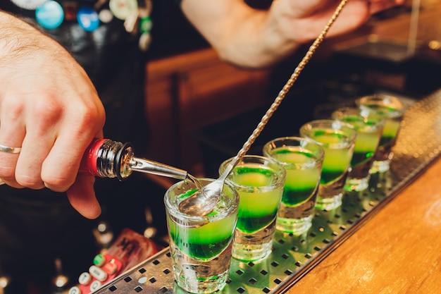 Barman maakt alcoholische schoten met rum en drank.