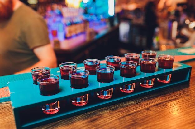 Barman maakt alcoholische schoten met rum en sterke drank.