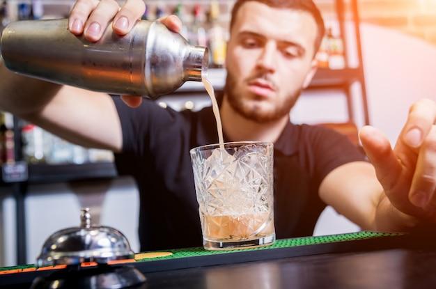 Barman maakt alcoholvrije cocktail aan de toog. verse cocktails. barman aan het werk. restaurant. nachtleven.