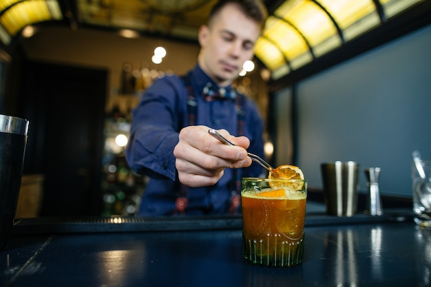 Barman maakt cocktail aan de bar.