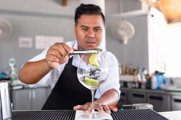 Barman maakt cocktail aan de tegenbar.