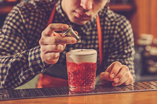 Barman maakt een alcoholische cocktail aan de bar op de bar