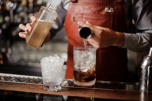 Barman maakt een alcoholische cocktail met ijs