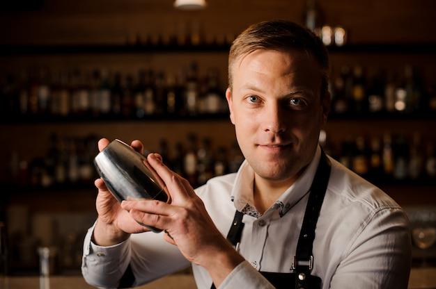 Barman maakt een cocktail met een shaker