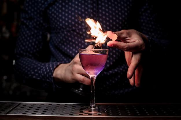 Barman maakt een zoete en frisse paarse zomercocktail met een rooknoot