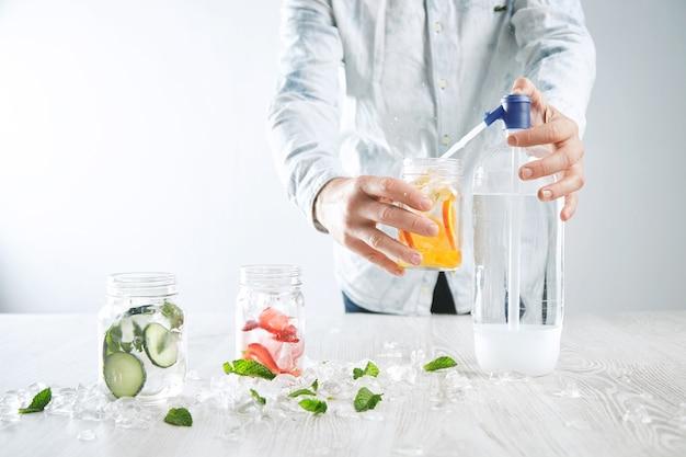 Barman maakt zelfgemaakte limonade, giet bruisend water in rustieke pot met stukjes sinaasappel