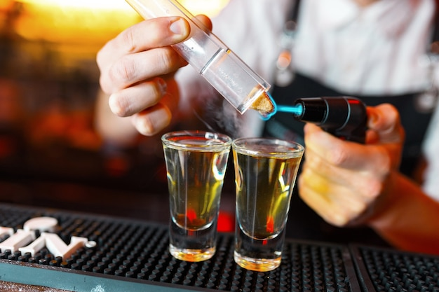 Barman man hete alcohol shots maken op de bar in de pub met een professionele brander. de barman steekt een aansteker boven een glas aan. ontspan in de nachtclub. hete vuurdranken. laat het feest