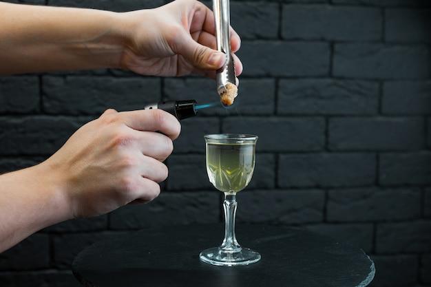 Barman man voorbereiding van een warme alcoholische cocktail in een bar op een zwarte houten tafel in de buurt van de bakstenen muur met behulp van een professionele brander. originele heerlijke cocktail.