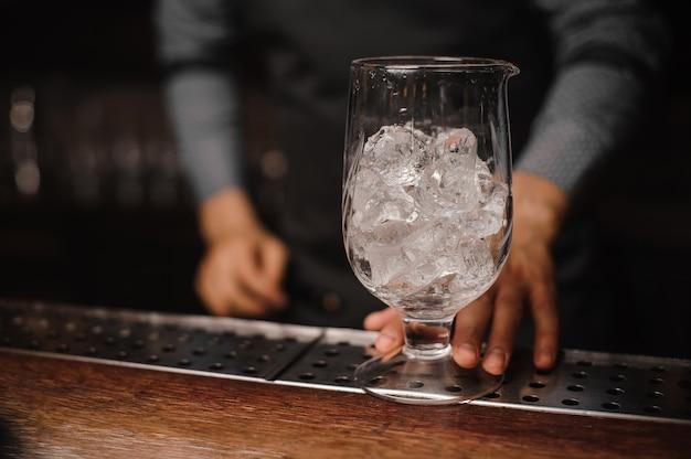 Barman met een glas gevuld met ijsblokjes