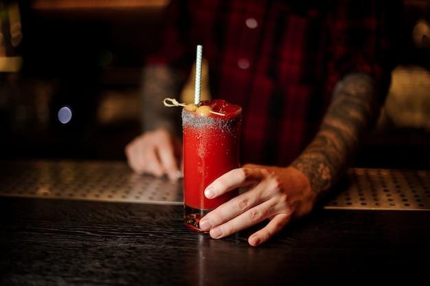 Barman met een glas zoute rode tomaat bloody mary cocktail versierd met zout en olijven met staw