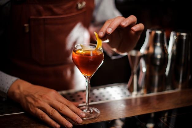 Barman met glas en citroenschil die cocktail voorbereiden bij bar