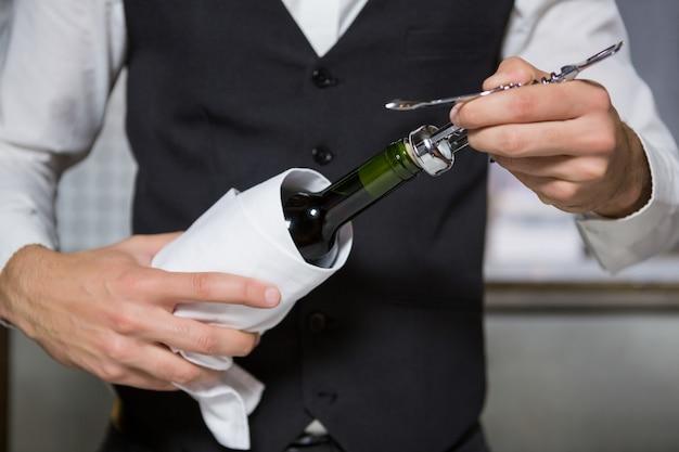 Barman met kurkentrekker om wijnfles te openen