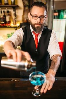 Barman met schudbeker die alcoholcocktail maakt