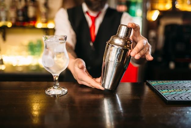 Barman met shaker achter een toog