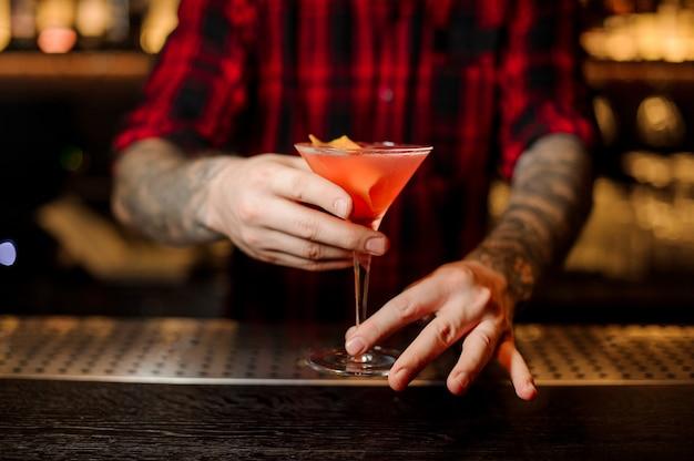 Barman met tatoeages met een frisse zoete alcoholische cocktail