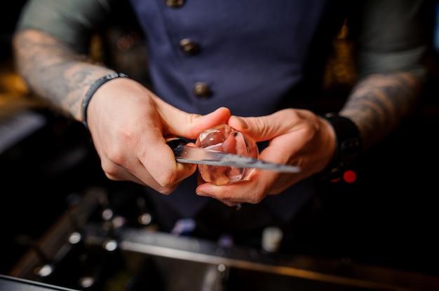 Barman met tatoeages op zijn handen snijdt het ijs met een speciaal mes