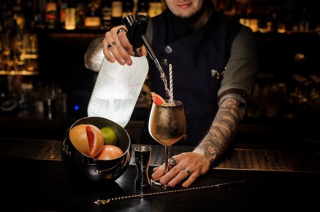 Barman met tattoo gieten koude frisdrank in het koperen cocktailglas