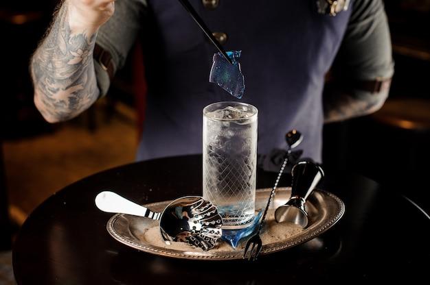 Barman met tattoo versieren verse en zoete zomercocktail met blauw stuk karamel op het dienblad