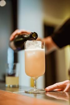Barman mousserende wijn gieten in een cocktailglas met pina colada. foto met ondiepe scherptediepte. verticaal levensstijlbeeld.