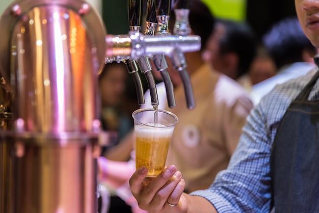 Barman of barman die een bier van bierkraan gieten