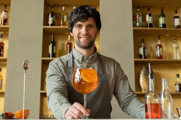 Barman passeert een glas oranje cocktail