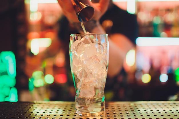Barman persen sap van verse limoen in een glas met behulp van citruspers en spatten het uit het maken van een alcoholische cocktail.
