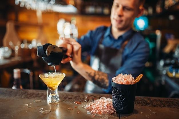 Barman perst citroen in het glas met ijs
