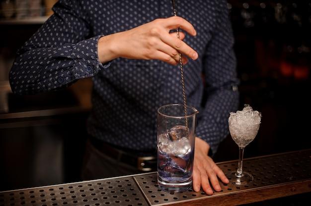 Barman roeren wodka met een blauwe siroop in een cocktailglas