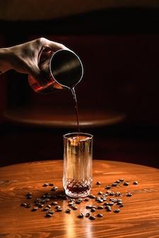 Barman schenkt een cocktail uit een shaker in een collins longdrinkglas met een ijsspeer. koffiebonen rond op een houten tafel.