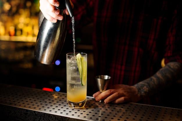 Barman schenkt een frisdrank in bij een lynchburg-limonadecocktail van de sifon in een glas op de toog