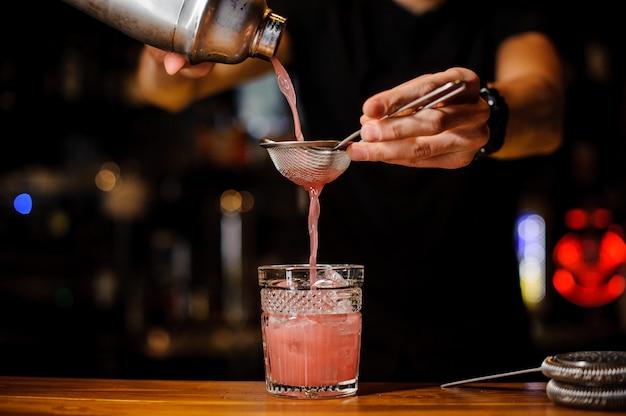 Barman schonk een alcoholische cocktail uit de shaker in een kristalglas