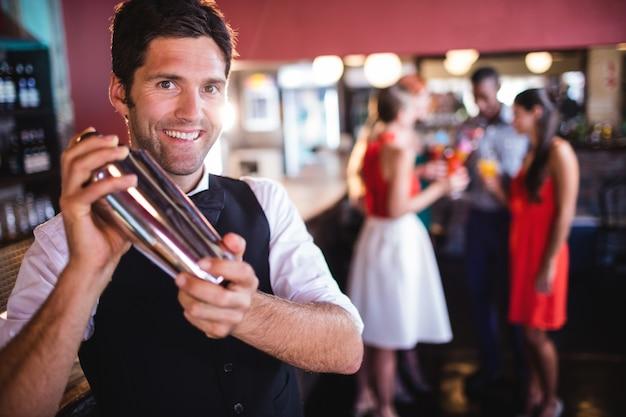 Barman schuddende cocktailmixer in nachtclub