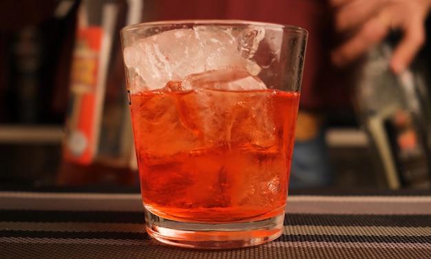 Barman serveert een cocktail aan de bar.