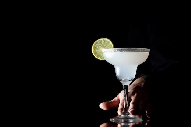 Barman serveert een klassieke margarita met limoen, hij houdt een cocktail in zijn hand op een zwarte achtergrond