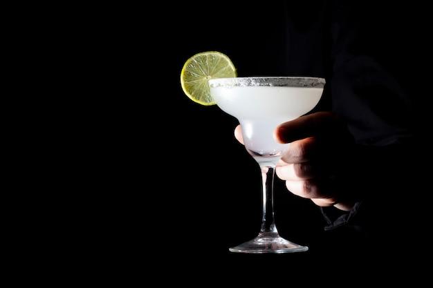 Barman serveert een klassieke margarita met limoen
