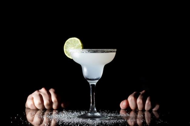 Barman serveert klassieke margarita met limoen op een zwarte achtergrond