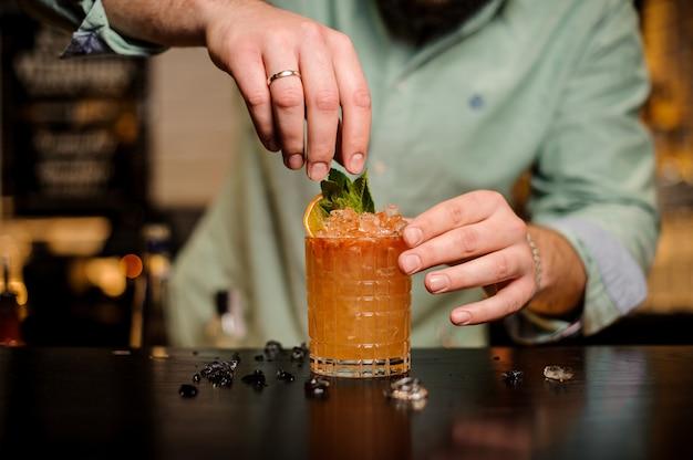 Barman siert een zomer cocktail zonder gezicht