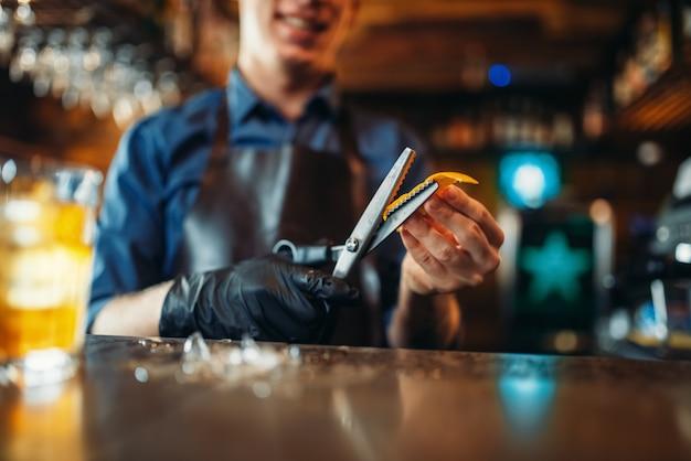 Barman sneed de korst van sinaasappels aan de toog