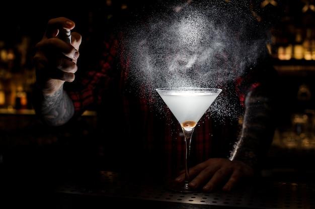 Barman sproeien bitter op het glas met verse cocktail