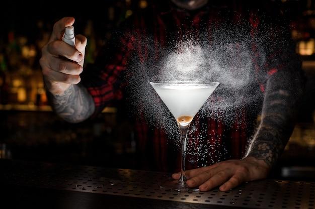 Barman sproeien bitter op het glas