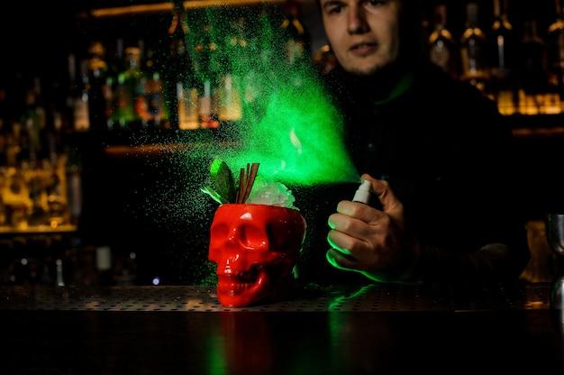 Barman sproeit op de cocktail in de rode scull-beker van de speciale verdamper in het groene licht op de toog.