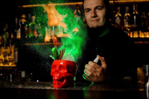 Barman sproeit op de cocktail in de rode scull-beker van de verdamper en vlam het in het groene licht op de toog