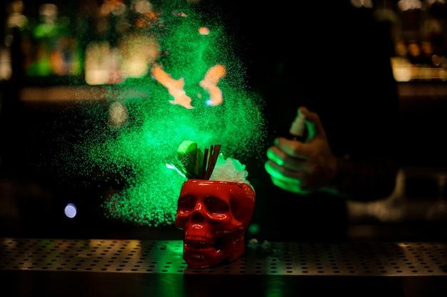 Barman sproeit op de cocktail in de scull-beker van de speciale verdamper in het groene licht op de toog