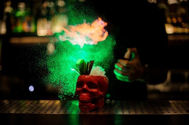 Barman sproeit op de cocktail in de scull rode kop van de speciale verdamper in het groene licht op de toog.