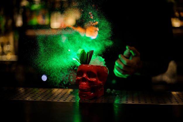 Barman sproeit op de heerlijke cocktail in de scull-cup uit de speciale verdamper in het groene licht op de bar.