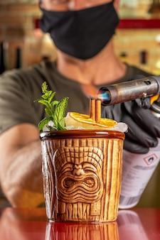 Barman steekt kaneel in brand in een tiki-cocktail aan de bar