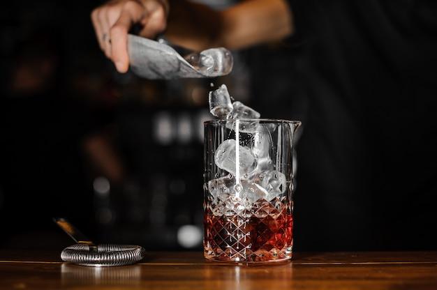 Barman stopt de ijsblokjes in een glas