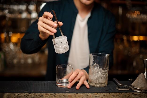 Barman stopt een groot stuk ijsblokje in een glas