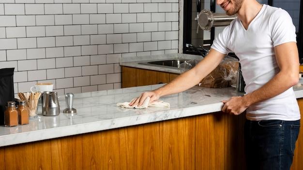 Barman veegt het werkblad met de doek af